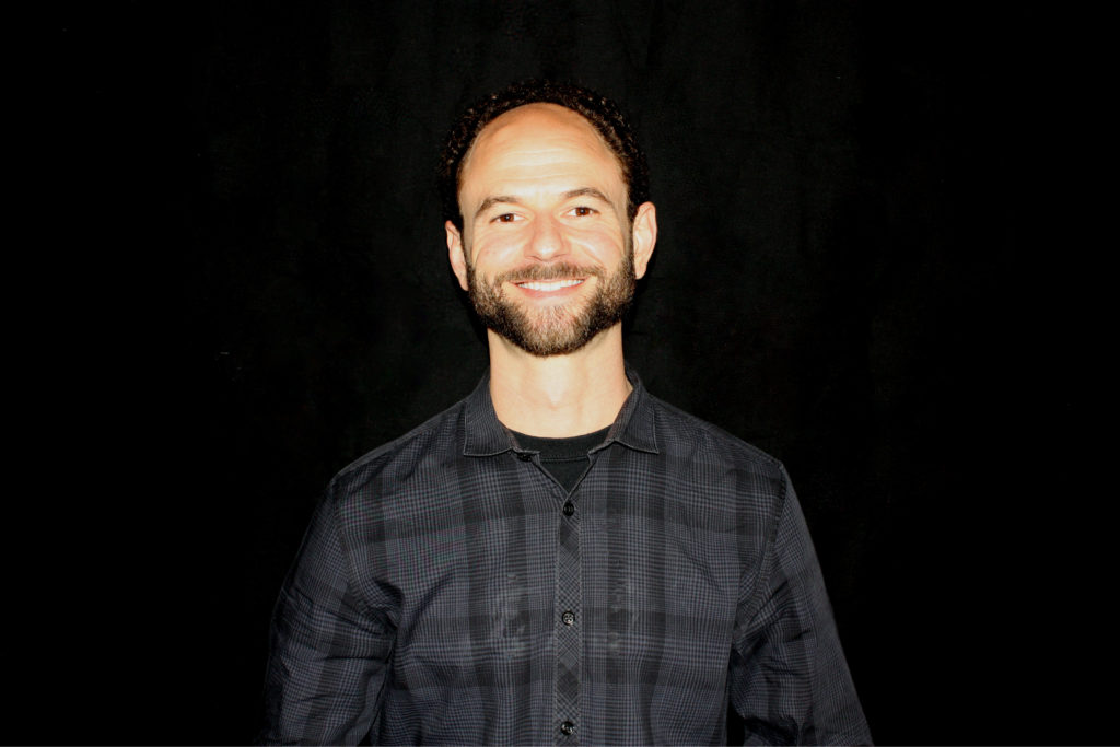 Andy Panayides, Director of Music Therapy for Opportunities for Positive Growth. Image description: Andy smiles against a black background. He is wearing a black and grey checkered button-down shirt and has a tight-trimmed beard.