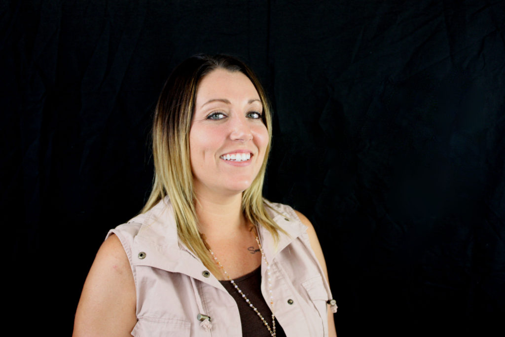 Raina Neal, Director of Behavioral Support Services for the Kokomo branch of Opportunities for Positive Growth. Image description: Raina smiles against a black background. She is wearing a black t-shirt, a light pink vest and a long gold necklace.