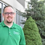 Sean Power, Employment Specialist Team Lead for Opportunities for Positive Growth. Image description: Sean smiles outside the Fishers O.P.G. office. He is wearing a green polo shirt with the O.P.G. logo and his signature glasses. In the background are blurred, green bushes.