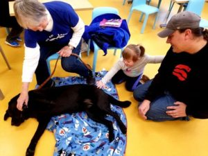 Image description: Harper, her father and a volunteer with Love on a Leash gently pet a black lab who lays on its side.