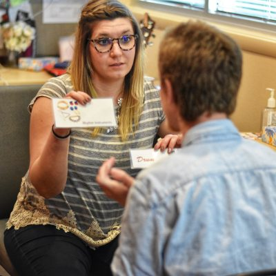 Image description: Carolyn holds up a flash card to a person supported in a music therapy session. His back is turned to the camera, but he looks at the card, making a decision.