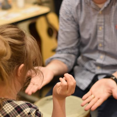 Image description: Justin's hands are extended to a young girl in his session. Her hands are lifted and she looks down at Justin's outstretched hands. Both peoples identities are hidden in the picture.
