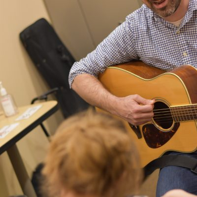 Image description: Justin is strumming his guitar and signing to a young girl. Her head is blurred in the forefront of the image.